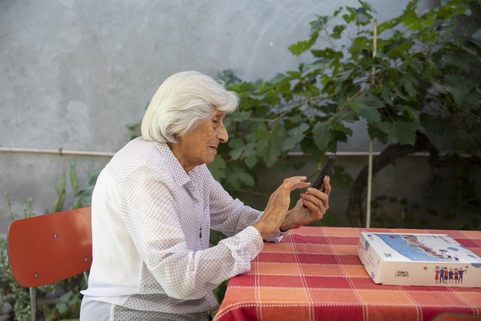 Una persona mayor sosteniendo un teléfono.